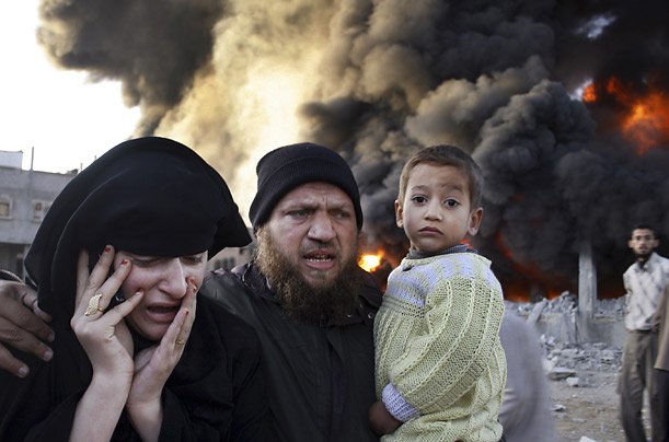 A Palestinian family rushes past a burning building after an Israeli missile strike in the Rafah refugee camp, southern Gaza