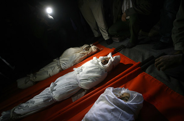 A torch lamp lights the bodies of three Palestinian boys from the same family who were killed in Rafah