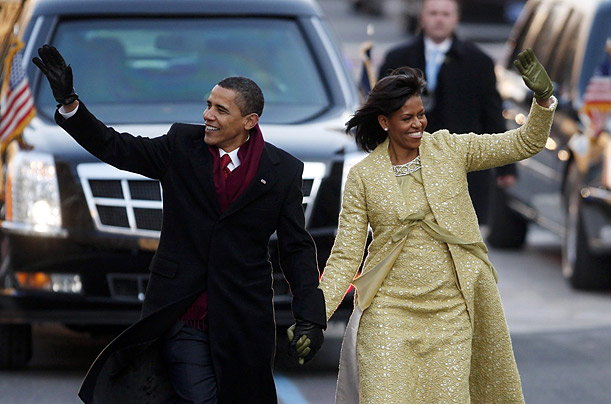 President Obama and his wife Michelle wave to the crowd as they walk down Pennsylvania Avenue in the Inauguration parade