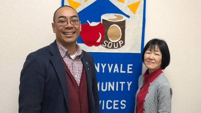 An older man and woman standing in front of a soup kitchen sign. Nonprofits, Next Avenue