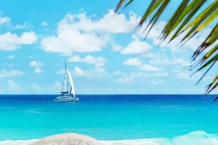A shot from the Anse Georgette beach on Praslin island of a yacht in the blue waters