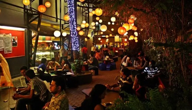 People sitting at the open roof Prithvi Cafe in Juhu