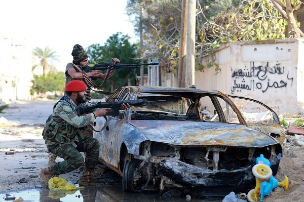 Pro-government Libyan forces, who are backed by locals, aim their weapons during clashes in the streets with the Shura Council of Libyan Revolutionaries, an alliance of former anti-Gaddafi rebels, who have joined forces with the Islamist group Ansar al-Sharia, in Benghazi December 28, 2014. REUTERS/Esam Omran Al-Fetori