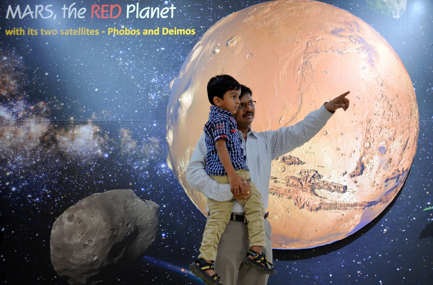 A father and his son look at information Tuesday about Mars at the Nehru Planetarium in Bangalore. (Manjunath Kiran/AFP/Getty Images)