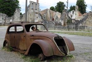 A young boy looks inside a rusted car body in a square near the remaining walls of buildings in the French martyr village of Oradour-sur-Glane, near Limoges, August 6, 2013. Six hundred forty-two inhabitants of Oradour-sur-Glane, men, women and children, were massacred by soldiers of a German Waffen-SS Panzer division who also destroyed the entire village on June 10, 1944. A new village was built nearby after the war, but the remains of the original village has been maintained as a permanent World War II memorial and museum. Picture taken August 6, 2013 REUTERS/Pascal Rossignol (FRANCE - Tags: SOCIETY CONFLICT)