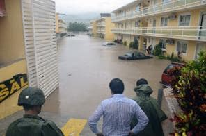 Army soldiers and a civilian look out into a flooded street caused by Tropical Storm Manuel in the city of Chilpancingo, Mexico, Sunday Sept. 15, 2013. In the southern Pacific Coast state of Guerrero, rains unleashed by Manuel resulted in the deaths of six people when their SUV lost control on a highway headed for the tourist resort of Acapulco. Another five people died in landslides in Guerrero and Puebla states, while the collapse of a fence killed another person in Acapulco. (AP Photo/Alejandrino Gonzalez)