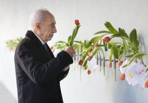 AMSTERDAM, NETHERLANDS - SEPTEMBER 29: Israeli President Shimon Peres places a tulip on the wall during his visit to the Dutch Theatre (Hollandsche Schouwburg) on September 29, 2013 in Amsterdam, Netherlands. The theatre was used as a location to deport Jews in the second World War and is now a monument. Peres is on an official four day visit to the Netherlands. (Photo by Michel Porro/Getty Images)