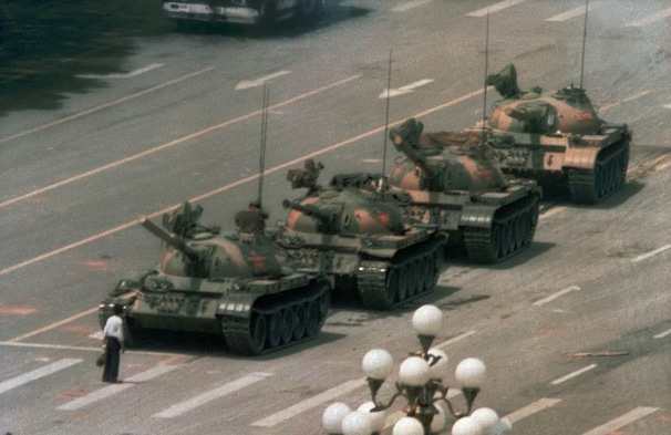 Iconic June 5, 1989, photo of a protester standing in front of tanks at Tiananmen Square. He was pulled away by  bystanders.