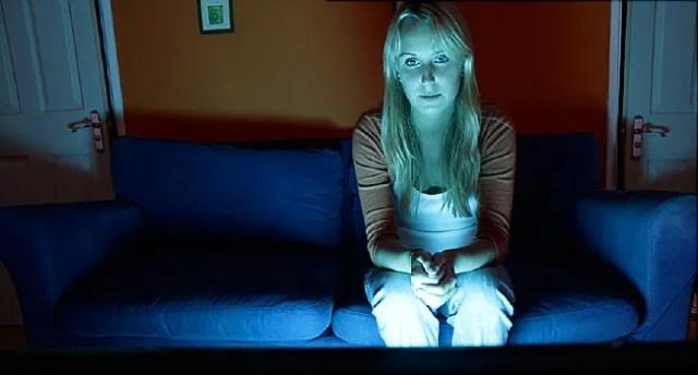 femme assise seule à regarder la télévision