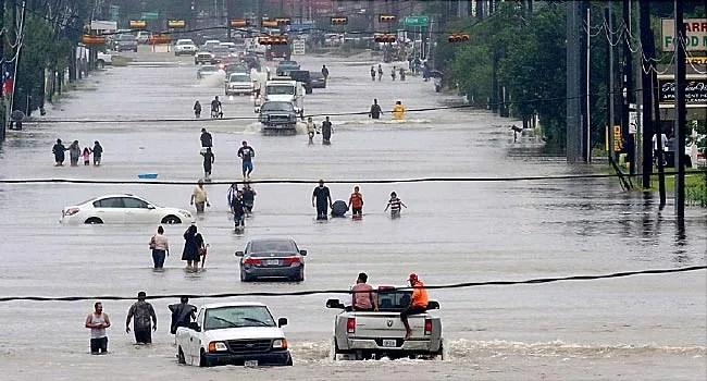 people walking through flood waters in houston