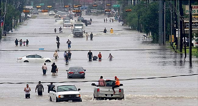 people walking through flood waters in houston