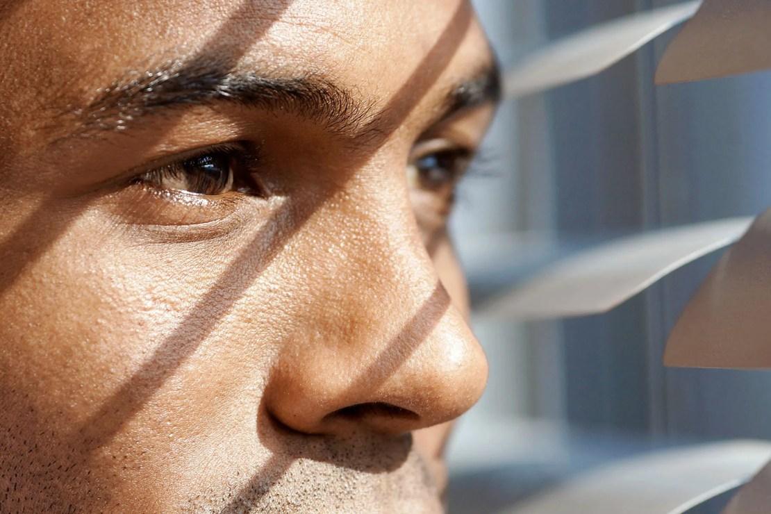 photo of man peering through blinds