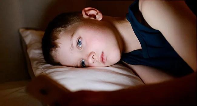 boy using smartphone at night