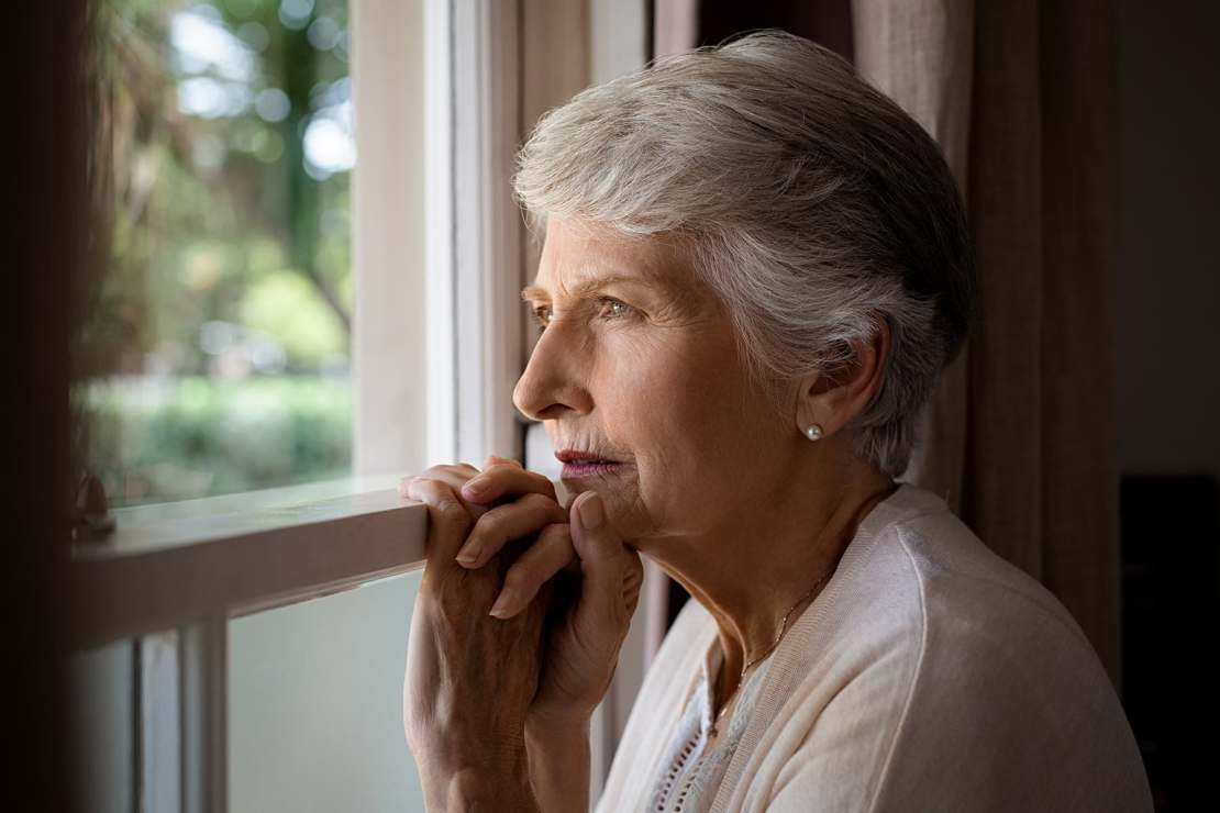 photo of mature woman looking out window