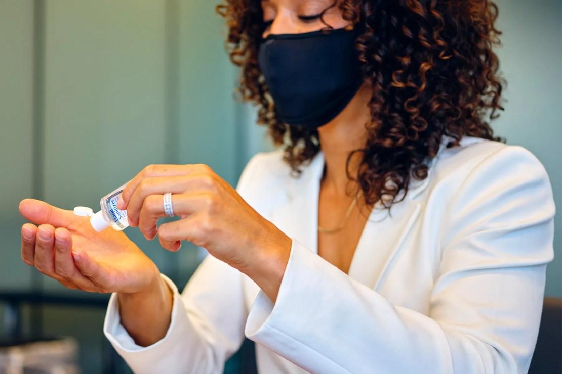 photo of woman wearing mask, using hand santizizer