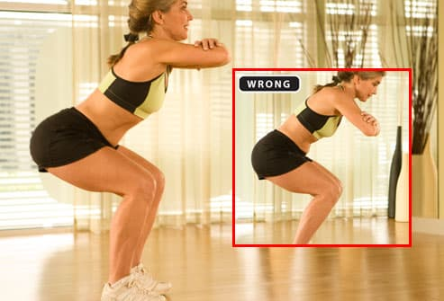 Trainer demonstrating proper form for squats
