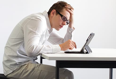 man hunched over tablet