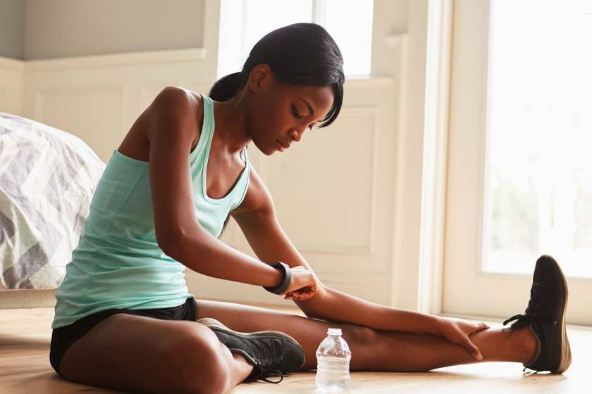 woman stretching and checking watch