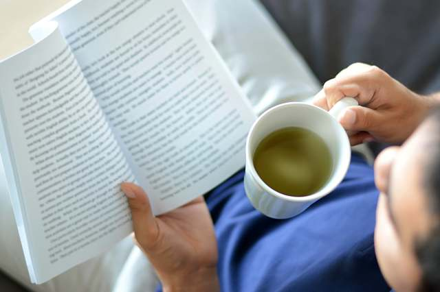 man reading book and drinking tea