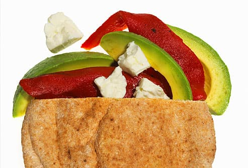 Wheat pita filled with peppers, avocado, and feta