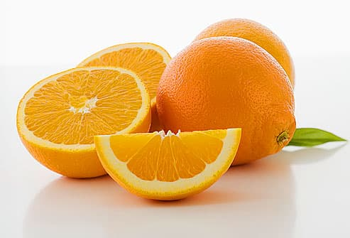 Whole and cut oranges, close-up