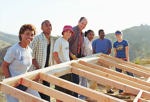 Group of people lifting wall of unfinished house