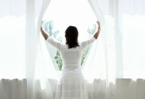 Woman opening curtains, looking out window