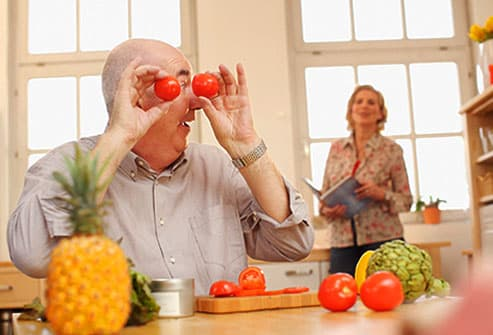 Mature man holding tomatoes up to eyes