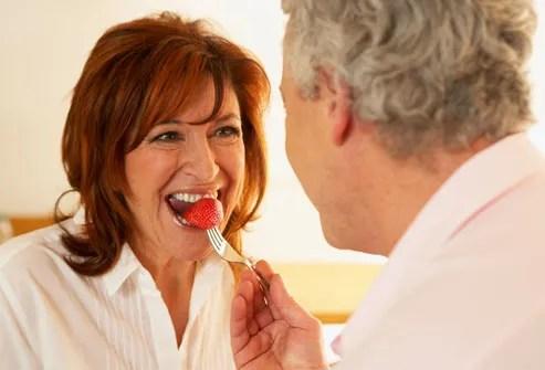 Man feeding woman strawberry