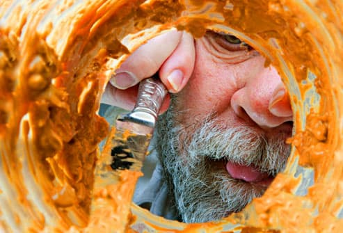 Mature man scraping peanut butter jar