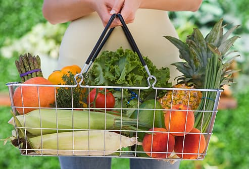 Woman holding basket of fruit and vegetables