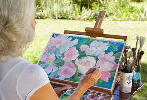mature woman painting flowers outdoors