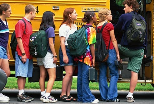 teens getting on school bus