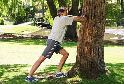 man stretching against tree