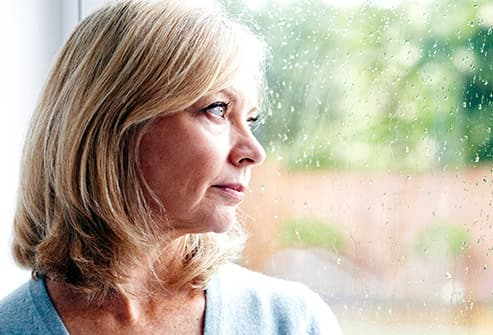 mature woman looking out glass door