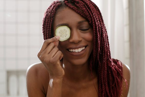 photo of woman with cucumber on eyes