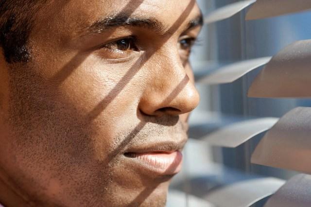 man looking through blinds
