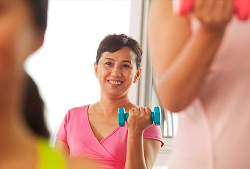 woman in exercise class with hand weights
