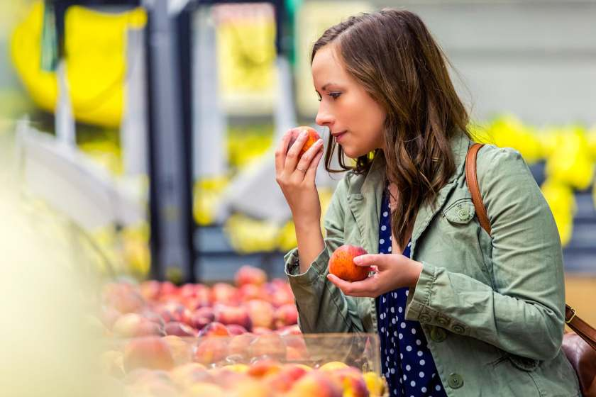 woman smelling peach