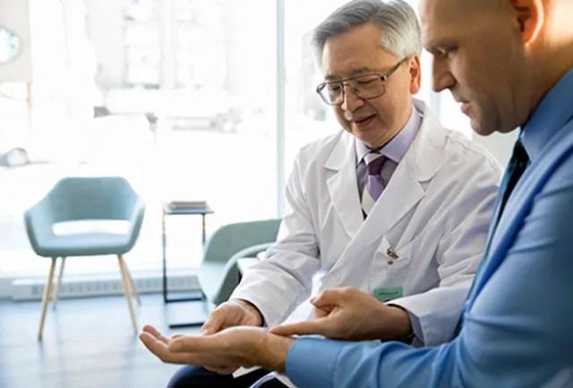 doctor examining mans wrist