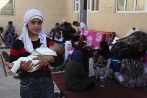 Ein syrisches Mädchen hält in einer Schule für die Flüchtlingskinder im irakischen Arbat seine kleine Schwester auf dem Arm