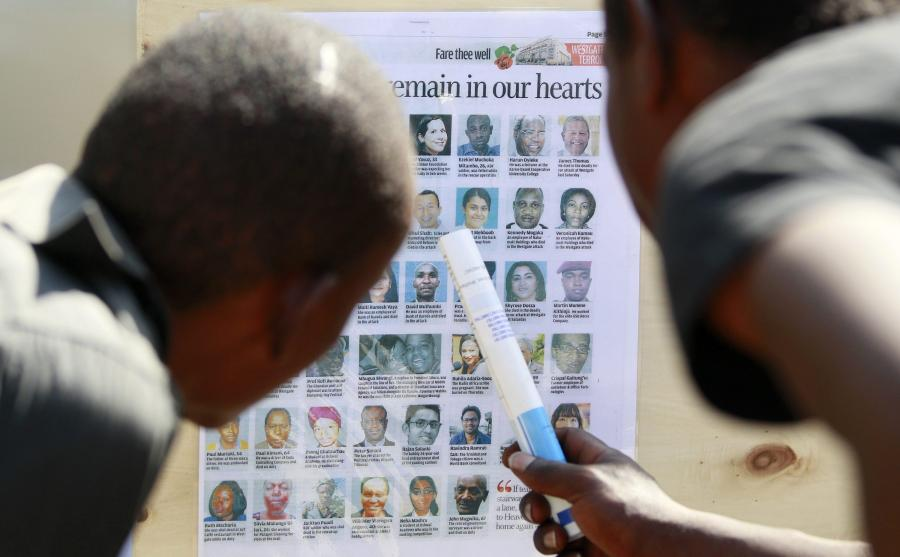 Men look at a newspaper cutting shows pictures of the slain victims who were killed in the recent Westgate shopping mall attack in Kenya's capital Nairobi