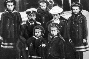 Die undatierte Archivaufnahme zeigt den letzten russischen Zaren Nikolaus II. und seine Ehefrau Alexandra Fjodorowna (geborene Alix, Prinzessin von Hessen-Darmstadt) mit ihren Kindern (von links) Olga, Alexej (vorn), Maria, Anastasia (vorn) und Tatjana. Die ganze Familie starb im Kugelhagel vor der im Bild oben aufgezeigten Wand.