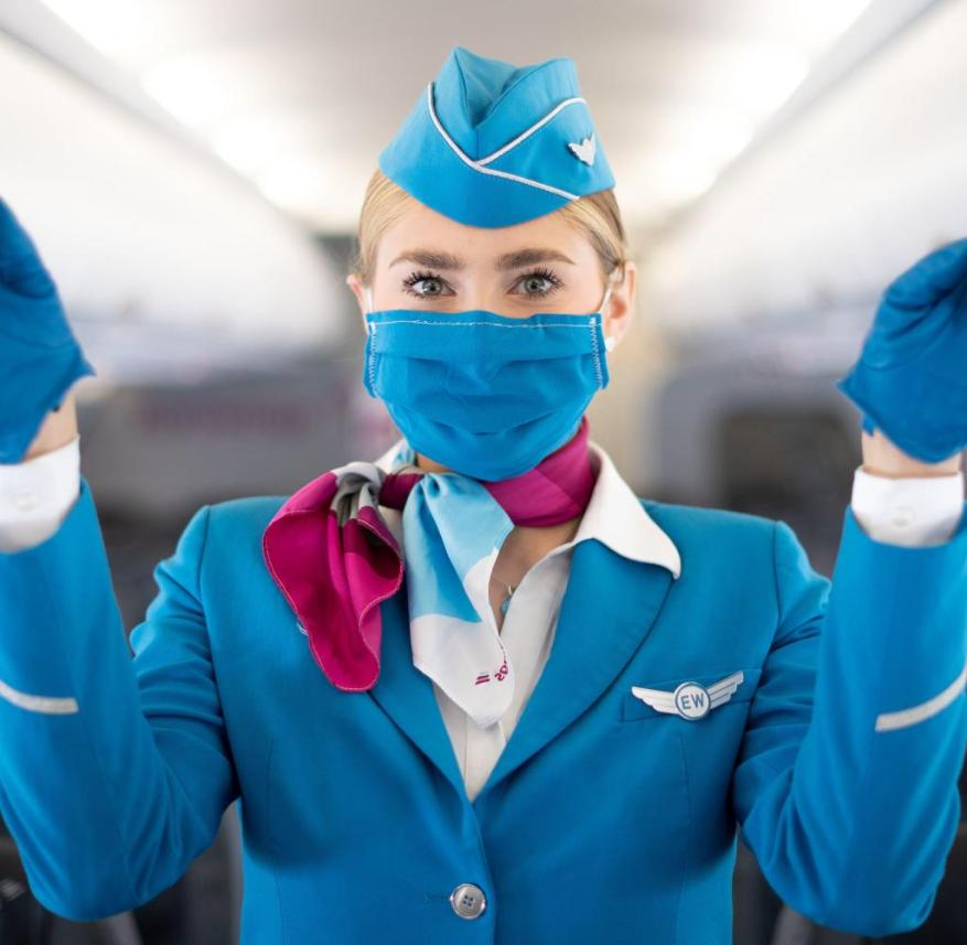 A flight attendant demonstrates the safety measures to protect against infection with Corona