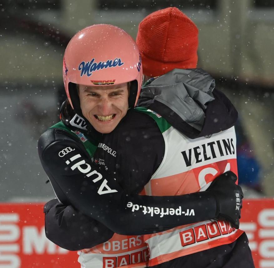 Karl Geiger celebrates his victory with team-mate Markus Eisenbichler