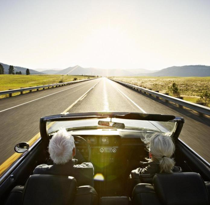 Senior couple driving convertible car at sunrise on rural highway