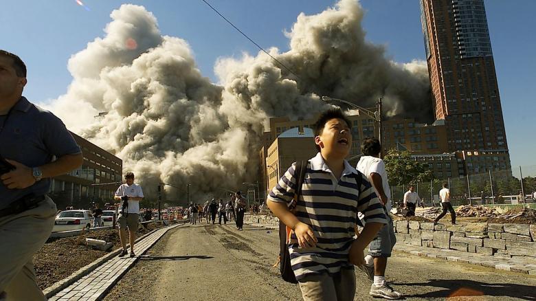 Menschen laufen davon, als der Nordturm des World Trade Centers in New York einstürzt