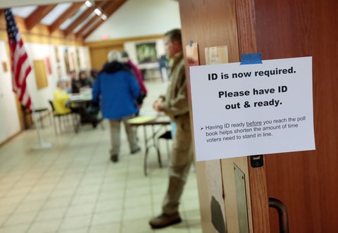A sign informs voters of the need for identification at the Olbrich Gardens polling location in Madison, Wis. Tuesday, Feb. 16, 2016. The Supreme Court election was the only statewide race in Tuesday's primary, which included scattered county and municipal races. Turnout was projected at only around 10 percent. A photo ID was required to vote, a new requirement stemming from a law first passed in 2011 but eventually put on hold until it was upheld by the state Supreme Court in one of several rulings seen as partisan in recent years.