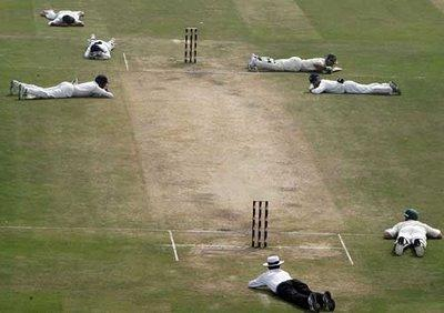 Cricketers and umpires lying on the floor