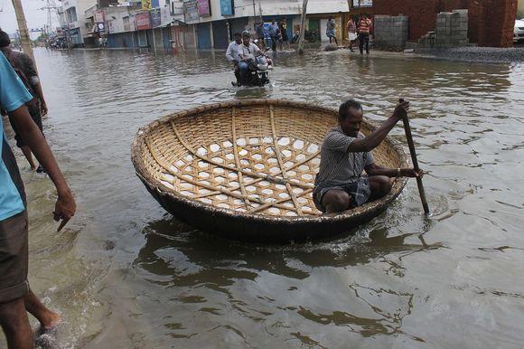 Mies meloo tulvavedessä pienellä bambuveneellä.